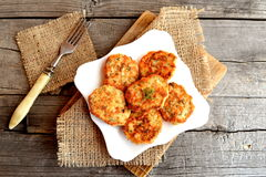 Fried fish cakes on a plate, fork on old wooden background. Cutlets from minced salmon. Delicious and nutritious lunch or dinner Royalty Free Stock Photography