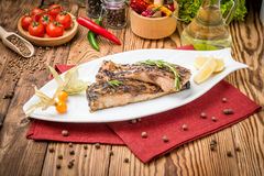 Fried fish carp on the grill. On a wooden table Stock Images