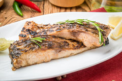 Fried fish carp on the grill. On a wooden table royalty free stock photography