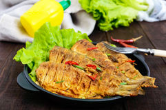Fried fish carp sazan on a cast-iron frying pan with lettuce leaves Stock Photography