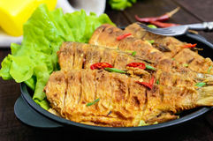 Fried fish carp sazan on a cast-iron frying pan with lettuce leaves Royalty Free Stock Photo