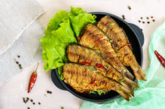 Fried fish carp sazan on a cast-iron frying pan with lettuce leaves Royalty Free Stock Images
