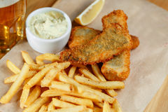 Fried fish and chips on a paper tray - Natural wooden background stock image