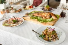 Fried fish and dishes on a banquet table in a restaurant. Follow depth of field, selective focus Royalty Free Stock Image
