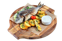 Fried fish dorade on wooden board with parchment and potatoes. Royalty Free Stock Image