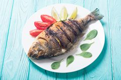 Fried fish dorado with lime , tomatoes and spinach . Sea food. Background royalty free stock photography
