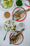 Fried fish dorado on the table. Fried Dorado fish, lettuce and vegetables on the table Stock Image