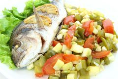 Fried fish dorado with vegetables and lemon. Close-up Stock Image