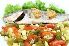 Fried fish dorado with vegetables and lemon. Close-up Royalty Free Stock Image
