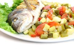 Fried fish dorado with vegetables and lemon. Close-up Stock Photography