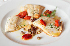 Fried fish fillet with capers and tomatoes Royalty Free Stock Image