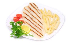 Fried fish fillet with fries and vegetables. Royalty Free Stock Photos