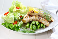 Fried fish fillet on green asparagus Royalty Free Stock Image