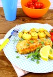 Fried fish fillet with rosemary potatoes and vegetables Stock Photography