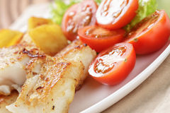Fried fish fillet with vegetables on wood table Royalty Free Stock Image