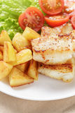Fried fish fillet with vegetables on wood table Royalty Free Stock Photos