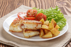 Fried fish fillet with vegetables on wood table Royalty Free Stock Photo
