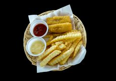 Fried fish and French fries with tomato sauce, cream sauce in the white wicker basket. stock images