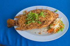 Fried fish with fried garlic on table Stock Image
