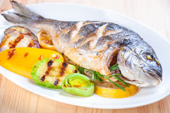 Fried fish with fried vegetables. On the plate Royalty Free Stock Image