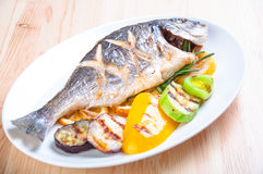 Fried fish with fried vegetables. On the plate Royalty Free Stock Photos