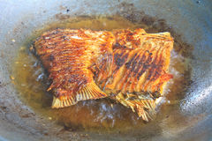 Fried fish in a frying pan Stock Images
