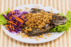 Fried fish with garlic on white plate Royalty Free Stock Photo