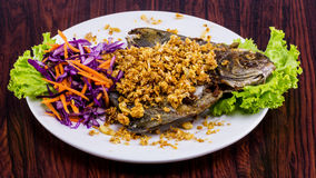 Fried fish with garlic on white plate Royalty Free Stock Photos