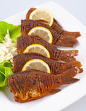 Fried fish with green salad, onions and lemon Stock Photography