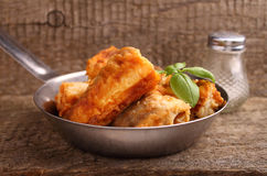 Fried fish hake in a frying pan. Decorated with basil Royalty Free Stock Photos