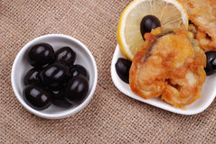 Fried fish with a lemon and olives Stock Photography