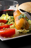 Fried fish with lettuce, lemon and tomato Stock Photography