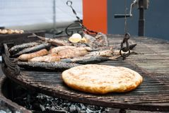 Fried fish, sausages, aromatic pita bread on the grill closeup stock photography