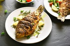 Fried fish on plate. Over black stone table royalty free stock images