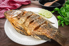 Fried fish on plate with vegetables and pan Stock Photo