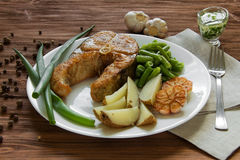 Fried fish with potatoes and asparagus Stock Photos