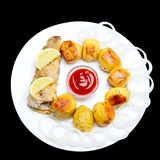 Fried fish with potatoes and chopped onions with ketchup. Isolat. E on a black background royalty free stock photos