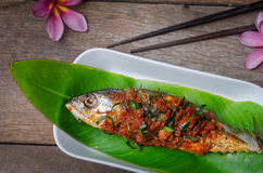 Fried fish in red curry sauce stock image