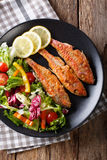 Fried fish red mullet with fresh vegetable salad close-up. Verti Stock Photography