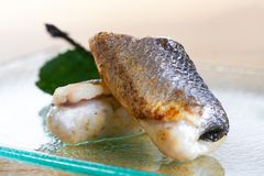 Fried fish roll on glass plate. Fresh seafood, closeup view on blurred background. royalty free stock photo