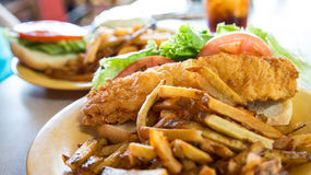 Fried Fish Sandwich with French Fries. A fried fish sandwich on a hoagie roll with fresh french fries, tomato slices and lettuce stock image