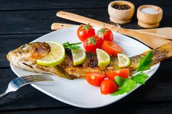 The fried fish served on the plate. Fried fish served on the plate Royalty Free Stock Image