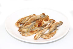 Fried fish smelt on the plate. On white background Stock Photos