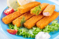 Fried Fish Sticks. Fish Fingers. Fish Sticks with lemon and sauces ready to eat stock photo