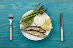 Fried fish with tartar sauce and asparagus shoots on a plate. Royalty Free Stock Photos