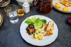 Fried fish,vegetable,lettuce and potoato salad on table with drink and food. Fried fish, vegetable,lettuce and potato salad on white plate on table with drink royalty free stock photography