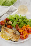 Fried fish with vegetables. And salad Stock Photo