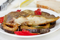 Fried fish with vegetables. On the white plate Stock Images
