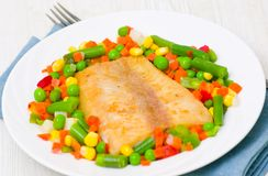 Fried fish with vegetables. On plate Stock Photo