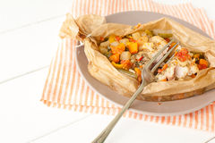 Fried fish with vegetables in parchment. On the plate Stock Photography